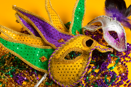 carnivale: A festive, colorful group of mardi gras or carnivale mask on a yellow background.  Venetian masks.