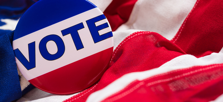 "admonition: A ""VOTE"" pin or button on a flag of the United States Stock Photo"
