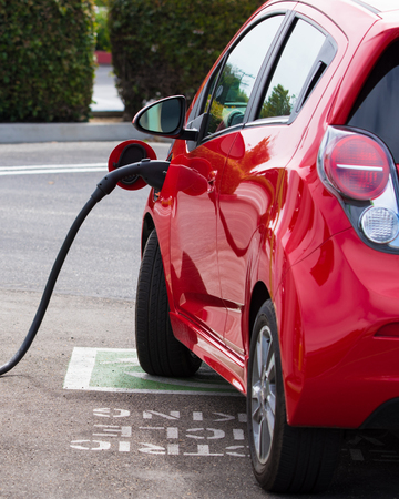 electric vehicle: An electric vehicle, car charging at a public station