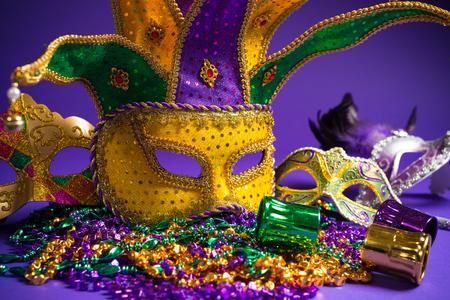 Feestelijke Groepering van mardi gras, Venetiaanse of carnivale masker op een paarse achtergrond Stockfoto