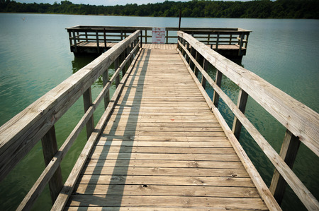 with no one: A fishing pier or dock on tranquil lake with no one.