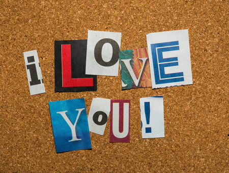 The message -I Love You- with cutout letters on a brown corkboard