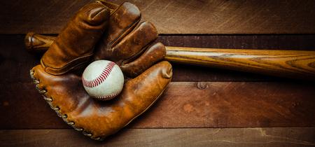A group of vintage baseball equipment, bats, gloves, baseballs on wooden background Stockfoto