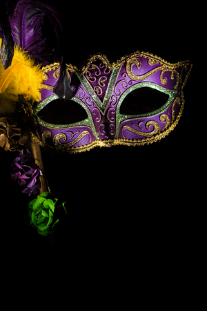 A purple mardi gras or venitian mask with feathers and flowers on a black background with copy space