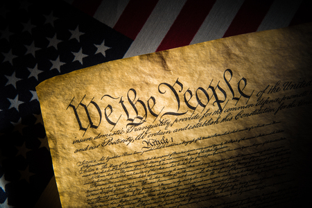 A copy of the Constitution of the United Sates of American on a flag of the USA