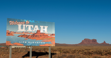 Welcome to Utah sign withblue sky and butte in the background