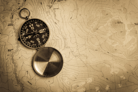 Manual compass on a topographical map with vintage look