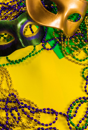 Two Mardi Gras mask with colorful beads on a yellow background Stock Photo