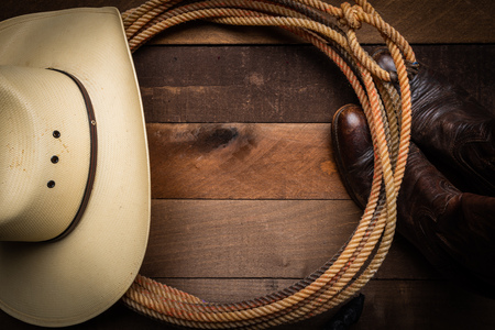 A cowboy hat, lariat rope and boots on a wooden plank background 写真素材