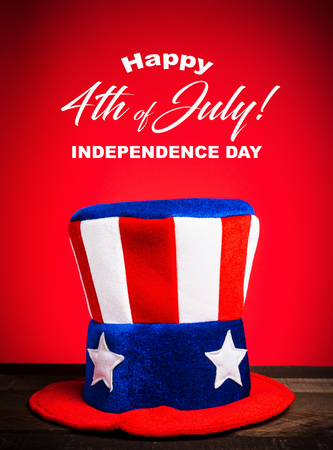 A felt colorful Uncle Sam hat on red background with Happy July 4th greeting