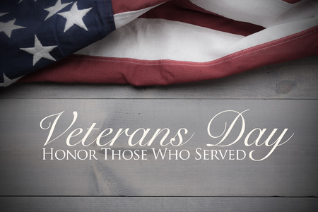 The flag of the United Sates of America on a grey plank background with Veterans Day greeting Stock Photo