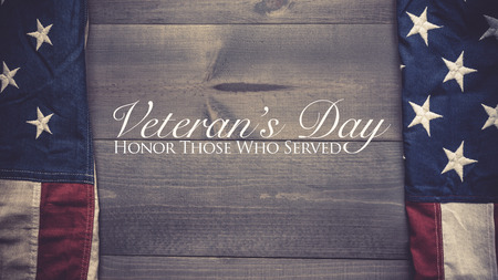 The flag of the United Sates of America on a grey plank background with Veterans Day greeting 写真素材