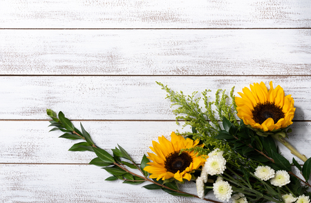 A Yellow sunflower arrangement on white wood background with copy space
