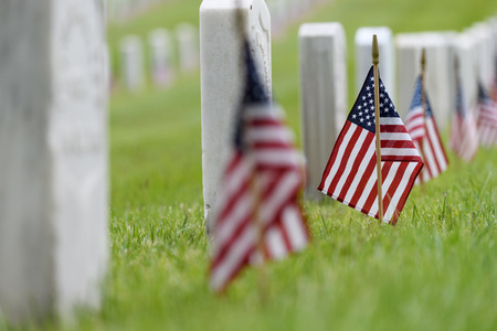 Small American flags and headstones at National cemetary- Memorial Day display 版權商用圖片