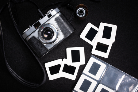 A classic, vintage film camera with a roll of film and numerous slides on a black background 免版税图像