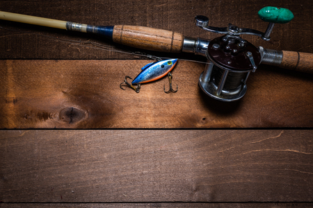A vintage fishing rod and reel, with a lure on a wooden plank background with copy space 免版税图像