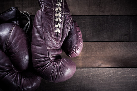 Pair of vintage, antique boxing gloves on a brown, slat wooden background