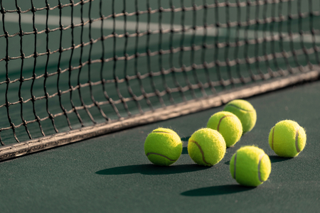 A group of yellow tennis ball on a court with net in background. Sports or exercise background.