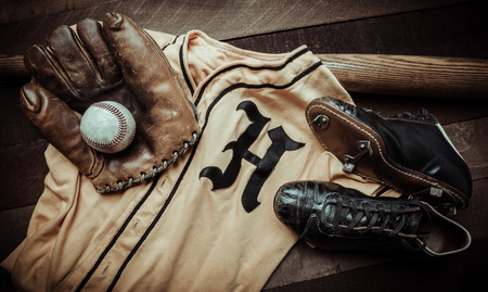 A group of vintage baseball equipment on a wooden background. Jersey is from a high school jersey in Arkansas and logo is not copyrighted. Imagens