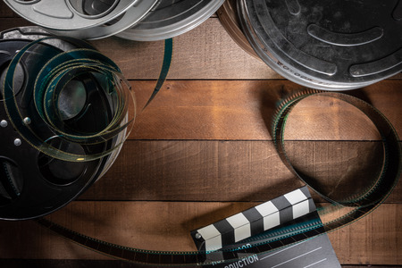 Multiple film reels and a clapboard on a wooden background. Film, Hollywood, entertainment industry objects 免版税图像