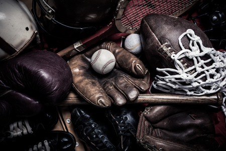 A large group of assorted vintage antique sports equipment. Including football helmet, baseball and boxing gloves etc.