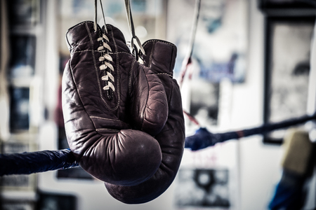 An old pair of boxing gloves hanging on the ropes in a boxing gym ring