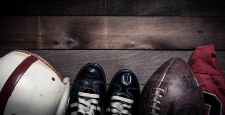 A group of vintage American football equipment on an aged wood background with copy space