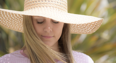 A young, pretty girl with a wide brimmed sun hat on a sunny day