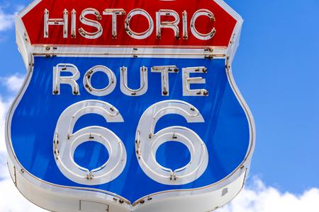 Rot-weiß-blaue Leuchtreklame an der berühmten, historischen Route 66 vor blauem Himmel Standard-Bild