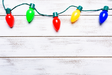A group of colorful christmas lights on a white background with copy space