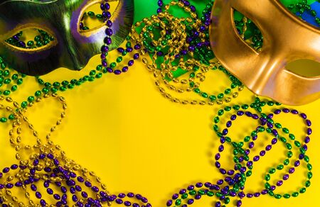 Two Mardi Gras mask with colorful beads on a yellow background 免版税图像