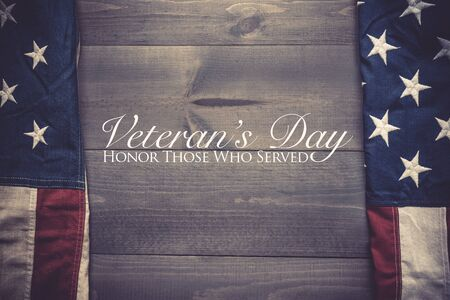 The flag of the United Sates of America on a grey plank background with Veterans Day greeting 版權商用圖片