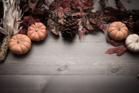 Fall, autumn pumpkins, leaves and veggies on a wooden background. Thanksgiving theme.