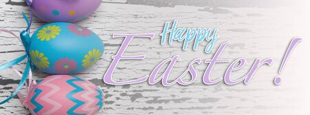 A group of pastel colored Easter eggs on a white, aged wooden background with greeting.
