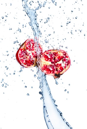 pomegranate juice: Fresh pomegranates with water splashing, isolated on white background  Stock Photo
