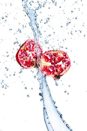 a pomegranate: Fresh pomegranates with water splashing, isolated on white background  Stock Photo