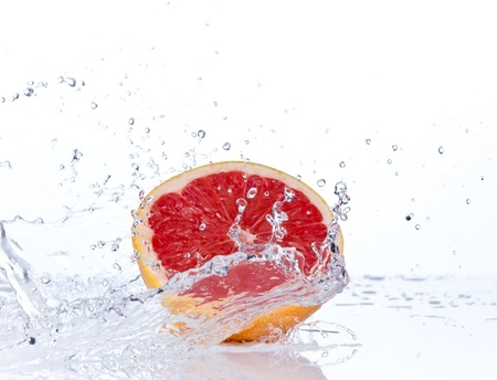 falling water: Fresh grapefruit slice in water splash, isolated on white background Stock Photo