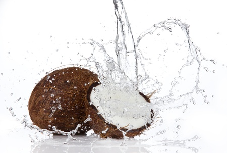coconut drink: Fresh coconuts in water splash, isolated on white background