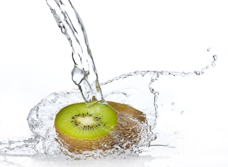 Fresh pieces of kiwi in water splash, isolated on white background photo