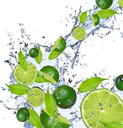 lime fruit: Limes pieces falling in water splash, isolated on white background  Stock Photo
