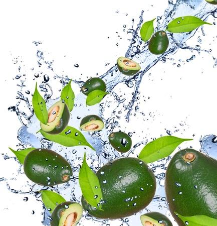 avocado: Avocado pezzi che cadono in spruzzi d'acqua, isolato su sfondo bianco Archivio Fotografico