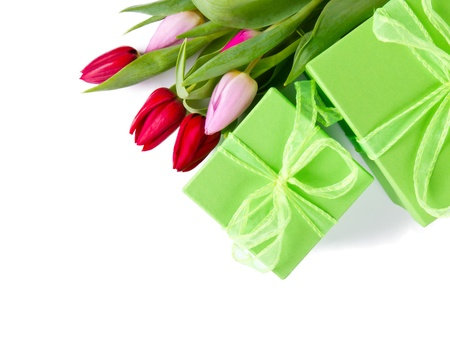 Fresh spring tulips with gifts, isolated on white background photo