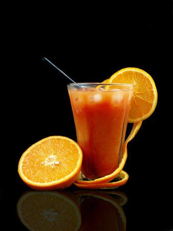 Orange drink on black background photo