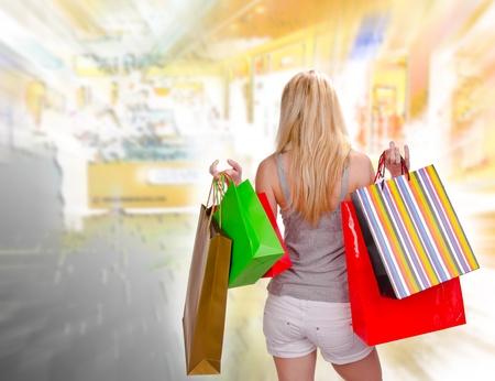 compras compulsivas: Mujer rubia con bolsas de compras en el centro comercial