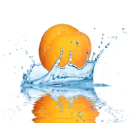 Apricot falling into water, isolated on white background photo