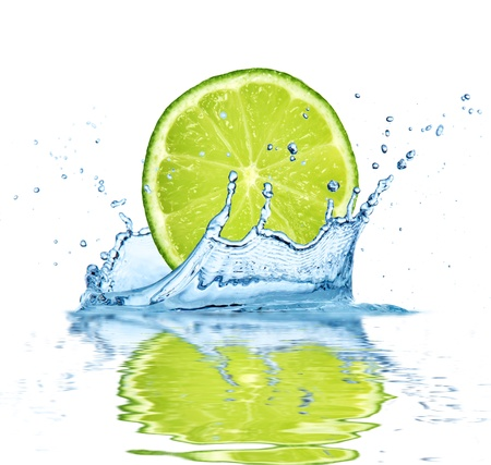 lime green background: Slice of lime falling into water, isolated on white background