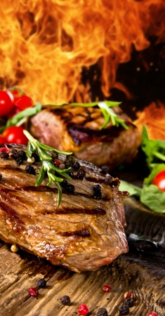 rubbing: Grilled beef steaks with flames on background