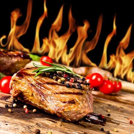 Grilled beef steaks with flames on background photo