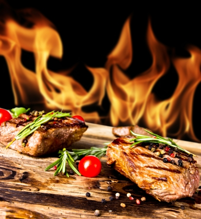 Grilled beef steaks with flames on background Stock Photo - 14006580