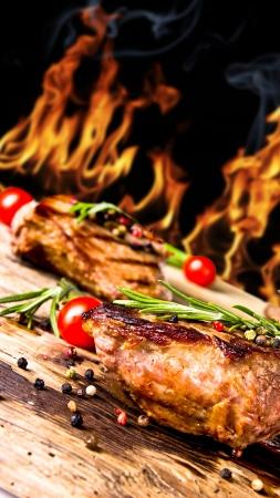 carne asada: Carnes a la parrilla de carne de vacuno con llamas en el fondo